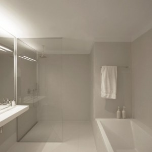 Dostęp do dużej łazienki jest możliwy tylko przez sypialnię gospodarzy – jest to przestrzeń zarezerwowana dla właścicieli. Dominują tu kamienne płytki (seria Déchirer Mutina zaprojektowana przez Patricię Urquiola) oraz szklane powierzchnie – w tym prawie niezauważalna przegroda prysznicowa (Dornbracht). Umywalka (Marieke) charakteryzuje się ciekawą formą i minimalnym zagłębieniem misy. Fot. i29 l interior architects.