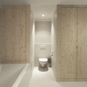 Toaletę ulokowano między wanną (oba sprzęty to marka Duravit) a drewnianymi schowkami, które swoim wyglądem ocieplają chłodne wizualnie wnętrze łazienki. Fot. i29 l interior architects.