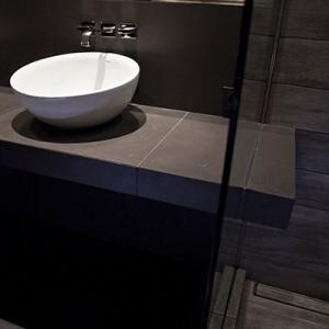 """Podumywalkowy blat """"przecina"""" taflę szkła oddzielającą strefę prysznica od reszty pomieszczenia. Połączenie dwóch części blatu dało wyjątkowy efekt wizualny oraz praktyczny w postaci półki na kosmetyki pod prysznicem. Odpływ liniowy Wiper """"Premium Pure"""", deszczownica Blue Water. Fot. Michał Łuczak."""