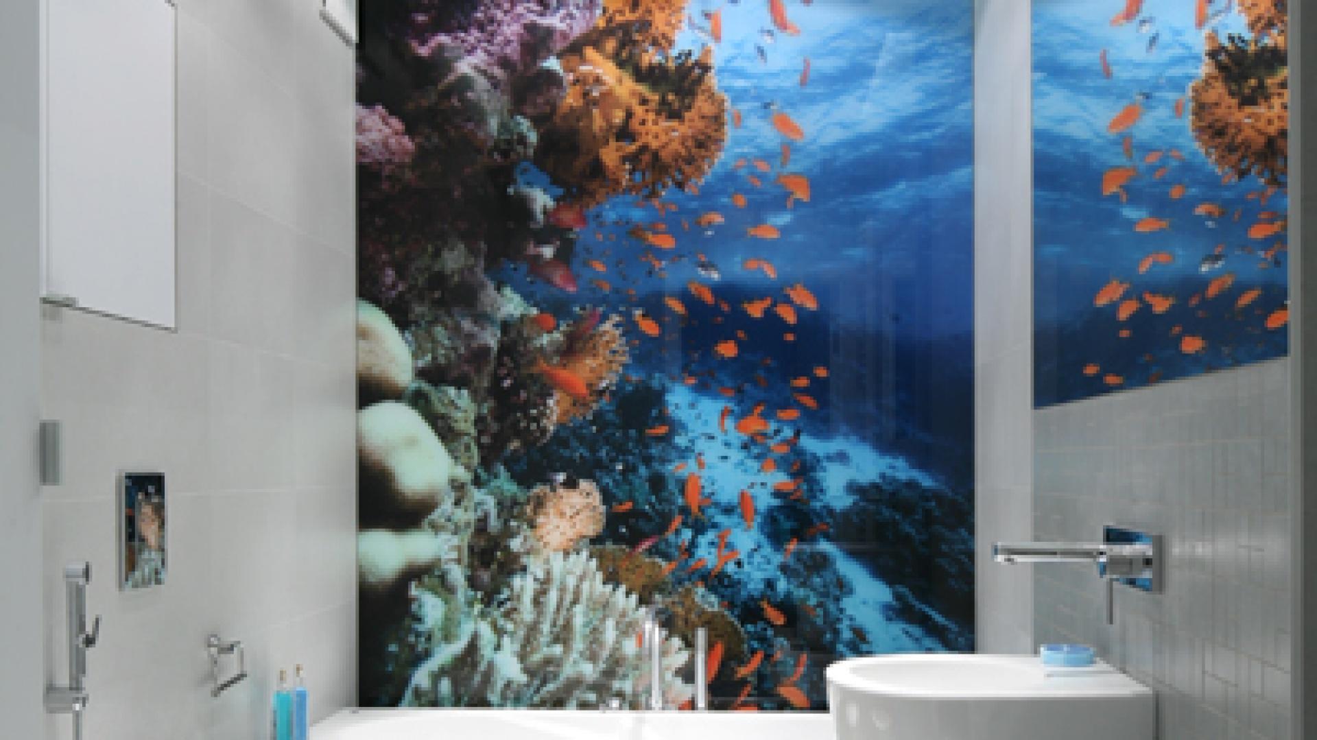 """Stonowane odcienie szarości są tłem dla najważniejszego elementu łazienki – zdjęcia rafy koralowej, która odbijając się w lustrze, dodatkowo potęguje efekt głębi. Płytki na podłodze i mozaika przy umywalce – NordCeram """"Gemini Grau"""", na ścianie – Rako """"Sandstone Plus Lappato"""". Fot. Bartosz Jarosz."""