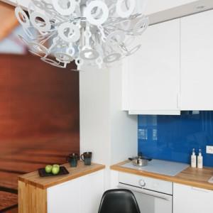 Ścianę między górną a dolną zabudową kuchenną, pomalowaną wcześniej na kolor niebieski,  zabezpiecza tafla szkła. Fot. Bartosz Jarosz.