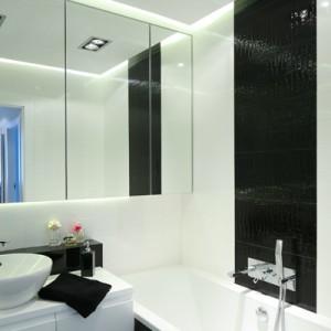 Łazienka utrzymana jest w biało-czarnej kolorystyce. Jej monochromatyczność przełamują jedynie ogromne lustra, dodatkowo powiększające niewielką przestrzeń. Fot. Bartosz Jarosz.