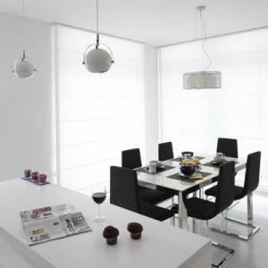 W jadalni, dzięki dużym oknom, zawsze jest jasno i słonecznie. Wykończone ciemoszarą tkaniną krzesła doskonale kontrastują z otaczającą je bielą. Fot. Bartosz Jarosz.