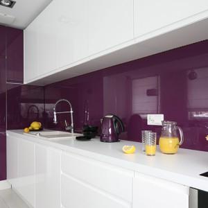 Zabudowa kuchenna wykonana została z lakierowanego MDF-u w dwóch kolorach: białym i fioletowym. Typowe uchwyty zastąpiły tu podfrezowania we frontach. Ściany między szafkami zabezpiecza szkło hartowane, lakierowane w kolorze fioletowym. Fot. Bartosz Jarosz.