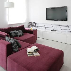 Panele laminowane w kolorze bielonego drewna, zastosowane w całej strefie dziennej oraz w sypialniach, do złudzenia przypominają jednolitą  powierzchnię. To zasługa ich wybarwienia oraz delikatnego rysunku drewna. Fot. Bartosz Jarosz.