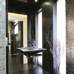 """Ściany toalety gościnnej pokrywa szklana mozaika Bisazza: w odcieniach czerni z kolekcji """"Nero Ebano"""" i """"Rachelle"""" oraz szarości – """"Elvira"""". W niszach ścian i sufitu jest ukryte oświetlenie LED. Fot. Bartosz Jarosz."""