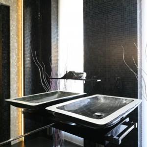"""Umywalkę (""""Alumix"""" Gardenia Orchidea), granitowy blat oraz baterię ścienną (Zazzeri) zainstalowano na lustrzanej ścianie. Zwierciadło odbija w nieskończoność wnętrze, dzięki temu, że naprzeciwko jest umieszczona druga ściana pokryta lustrem. Fot. Bartosz Jarosz."""
