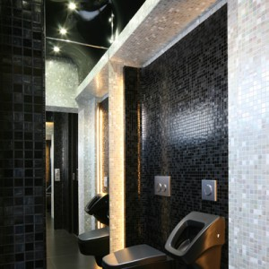 """Sedes i pisuar (seria """"SPA"""" Kerasan) są prawie niewidoczne na tle ściany wykończonej mozaiką w odcieniach czerni. Toaleta ma wysokość dwóch kondygnacji – czarny sufit napinany wybrano z oferty Barrisol. Fot. Bartosz Jarosz."""