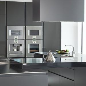 Dolna zabudowa jest wykończona w półmacie, zaś wysoka – połysku, co nadaje kuchni wyrafinowanej elegancji. Do ich antracytowego koloru dopasowano urządzenia AGD marki Gaggenau. Fot. Norbert Banaszyk.