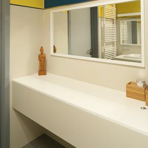 Meble wykonane zostały z MDF-u lakierowanego na  kolor identyczny z kolorem pytek ściennych; blaty z Corianu. Większa szafka pełni również rolę toaletki. Fot. Bartosz Jarosz.