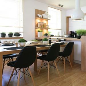 Umowną granicę pomiędzy kuchnią a jadalnią stanowi półwysep. Przy nim ustawiono duży stół oraz komplet  nowoczesnych krzeseł (Agata Meble), których czarna tapicerka oraz drewniany stelaż doskonale uzupełniają całość aranżacji. Fot. Bartosz Jarosz.