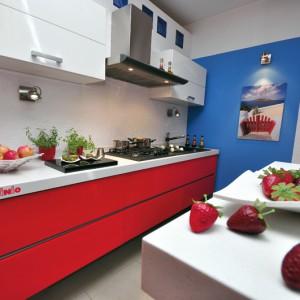 Kuchnia 1 – nowoczesna, prosta w formie kuchnia połyskowa, w której przeciwwagą dla białych frontów szafek wiszących jest ognista czerwień w dolnych szufladach; ten dynamiczny kontrast uzupełnia błękit na ścianie; świetnie nadaje się do małych pomieszczeń. Wycena indywidualna, Pinio.