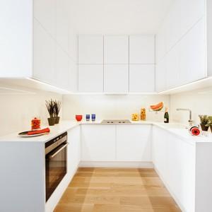 Zabudowę kuchenną wykonano z białego, lakierowanego MDF-u. Górne szafki otwierają się bezuchwytowo, dolne mają uchwyty wpuszczone we fronty. Ścianę nad blatem zabezpiecza tafla białego szkła. Fot. Ghalemco Poland.