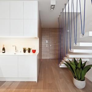 Na podłodze w całej części dziennej położony jest bielony dąb. Drewno (dębowy fornir) wykorzystano także do wykonania zabudowy szafy. Tłem dla mebli są jednolite, białe ściany. Fot. Ghalemco Poland.