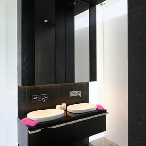 Strefy łazienki zostały umieszczone w jednym pasie. Podłoga oraz ściany działowe wykończone antracytowym gresem oraz podwieszany sufit tworzą oryginalną ramę. Fot. Bartosz Jarosz.