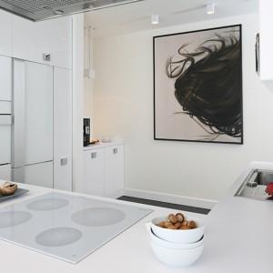 Elegancka kuchnia zaprojektowana zgodnie z aktualnymi trendami: białe, akrylowe fronty, wyraziste uchwyty, szafki górne do sufitu. Fot. Bartosz Jarosz.