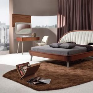 Łóżko z kolekcji Dolce, utrzymane w stylistyce retro.  Uroku dodaje mu orzechowy fornir i zagłówek tapicerowany w skórze naturalnej. Cena: ok. 5.800 zł (160 cm), Woodways.