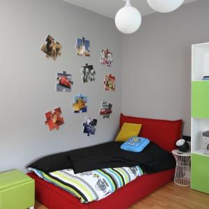 Podstawą każdego dziecięcego pokoju, niezależnie od wieku właściciela, jest wygodne łóżko. W jego sąsiedztwie ustawiono mały, metalowy stoliczek, na który można odłożyć książkę czy telefon komórkowy. Ścianę zdobią oryginalne obrazy przypominające formą puzzle. Fot. Bartosz Jarosz.