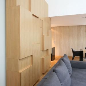Drewniany kubik podzielony na kwadraty i prostokąty o różnej grubości pełni zarówno funkcję ozdobną, jak i praktyczną. Skrywa pojemne, głębokie szafki. Fot. Bartosz Jarosz.