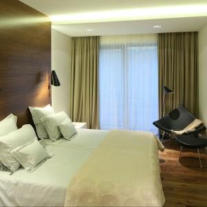 Drewno na ścianach i podłodze, zasłony oraz różna konfiguracja oświetlenia tworzą w sypialni ciepły, relaksujący klimat. W rogu fotel Coconut Vitry. Fot. Bartosz Jarosz.