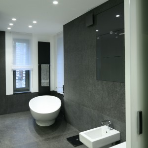 Łazienka w całości wykończona jest szarym bazaltem, co podkreśla jej minimalistyczny charakter. Podobnie jak schowane w ścianach szafki. Nic nie stoi na widoku. Fot. Bartosz Jarosz.