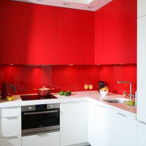 Zabudowa kuchenna została zaplanowana w kształcie litery L. Wykonana jest z MDF-u wykończonego matowym lakierem – czerwonym i białym. Nad blatem czerwone szkło lakierowane, blat z konglomeratu kwarcowo-granitowego. Fot. Bartosz Jarosz.