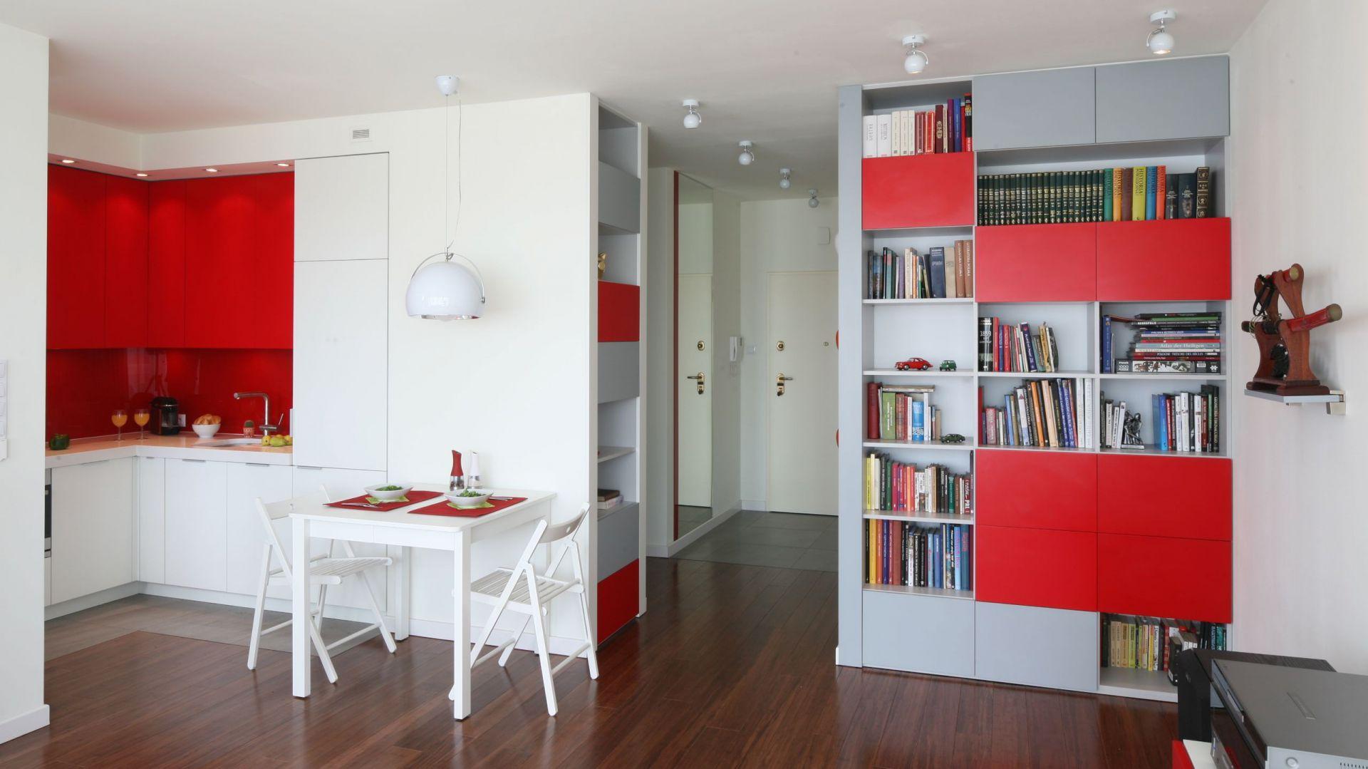 Całe mieszkanie urządzone jest w jednolitej stylistyce i palecie kolorów. Czerwono-biały aneks kuchenny stanowi jego integralną część. Fot. Bartosz Jarosz.