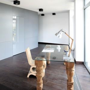 Biurko łączy funkcje użytkowe z dekoracyjnym. Blat wykonany jest ze szkła, natomiast nogi (każda z nich jest inna) wyrzeźbił Paweł Grunert. W tle widoczny jest szary kubik, skrywający łazienkę. Fot. Bartosz Jarosz.