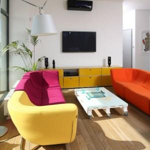 Szklane ściany stały się również doskonałym tłem dla głównych elementów salonu – mocnej, kolorowej kanapy oraz systemowych mebli USM Haller. Fot. Bartosz Jarosz.