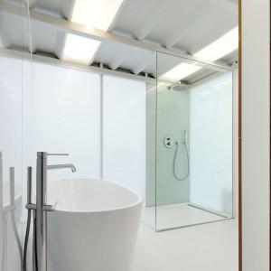Minimalistyczna łazienka została wyposażona w imponującą, nowoczesną wanną wolno stojącą. Fot. adn architectures.