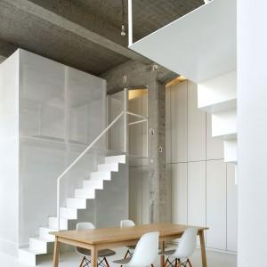 W otwartej przestrzeni studio wydzielono tylko łazienkę, sypialnię i pokój pracy. Prowadzą do nich minimalistyczne, piękne schody. Fot. adn architectures.