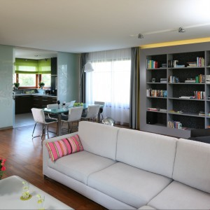 W salonie znalazła się również nowoczesna szara biblioteczka. Idealnie koresponduje z nią jasny odcień kanap oraz ciepłe drewno podłogi. Fot. Bartosz Jarosz.