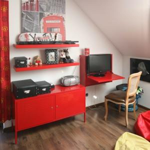 Czerwona komoda i półki dają nastolatkowi miejsce, jakie miałby w standardowym modelu biurka. Fot. Bartosz Jarosz.