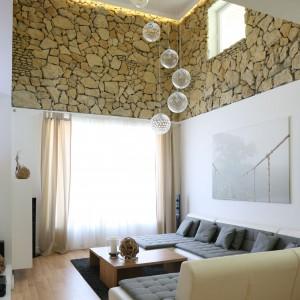 Salon ma wysokość dwóch kondygnacji. Ściany od połowy wysokości wykończone kamieniem, wydobytym podczas renowacji budynku. Fot. Bartosz Jarosz.
