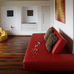 Czerwona sofa i żółte siedzisko wnosi do białego biurowego wnętrza trochę stylistycznego luzu. Fot. Marcin Onufryjuk.