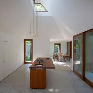 Kuchnia - pochwała prostoty. Nad wyspą kuchenną uwagę zwraca minimalistyczne oświetlenie. Fot. Sebastian Zachariah.