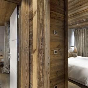 Jedna z kilku znajdujących się w domu sypialni - podobnie jak w pokoju dziennym stanowią inspirujące połączenie rustykalnej stylistyki i modernistycznego charakteru. Fot. Chalet Eden Courchevel.