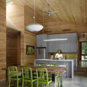 Jadalnia to efektowna część domu - dzięki pięknemu drewnianemu stołowi, kolorowym zielonym krzesłom i umiejętnie dobranemu oświetleniu jadalnianego stołu. Fot. Shai Gil.