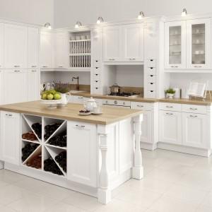 Bogato zdobiona kuchnia Villa II o nieregularnych kształtach w kolorze białym. Klasyczny lity dębowy front ramiakowy wzbogacony o liczne dodatki: pilastry, kolumny, głowice, zdobne listwy wieńczące, regały na wino i talerze oraz drewniane szufladki i witryny. Blat ma wzór naturalnego dębu. Wycena indywidualna, WFM Kuchnie.