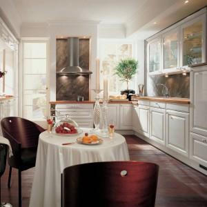 Rodzinna kuchnia Alnopol w klasycznym wydaniu. Fronty w kolorze białym lakierowane na wysoki połysk ładnie odbijają światło. Całość uzupełniają ciepłe, drewniane blaty. Wycena indywidualna, Alno.