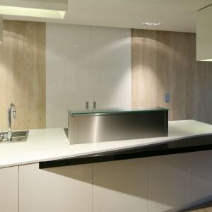 Przesuwane drzwi dzielące kuchnię na części reprezentacyjną i bardziej roboczą wykończone zostały białym, lakierowanym MDF-em, tworzącym spójną całość z trawertynem zastosowanym na ścianach. Fot. Bartosz Jarosz.
