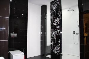 Biało-czarna łazienka – duży prysznic z miejscem do siedzenia i kolorystyka zapewniająca nieprzemijającą elegancję – biel i czerń z odrobiną czerwieni. Fot. Studio BB Architekci