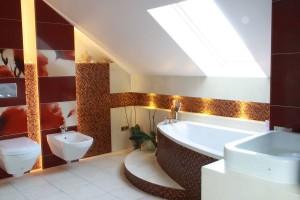 Przytulna łazienka z wanną umieszczoną na stopniu. Duże maki nadają jej nieco romantyczny charakter, a ciepłe barwy w połączeniu ze specyfiką przestrzeni poddasza tworzą przyjazny klimat sprzyjający odpoczynkowi. Fot. Studio Architekci BB