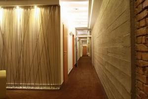 Dekoracja korytarza hotelowego wykonana według indywidualnego projektu. Oryginalny element wystroju stanowią podświetlane pręty ze stali nierdzewnej.  Połączenie stali, betonu i cegły nadaje wnętrzu hotelu nieco industrialny charakter. Fot. Studio BB Architekci