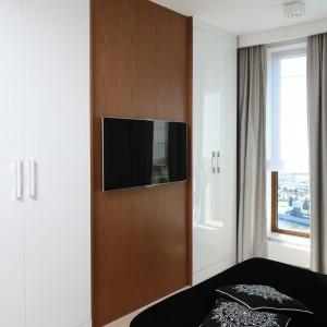 Obok telewizora umieszczonego na ścianie z rysunkiem drewna, znajdują się dwuskrzydłowe pojemne szafy, ukryte za połyskującymi frontami. Proj. Anna Maria Sokołowska. Fot. Bartosz Jarosz.
