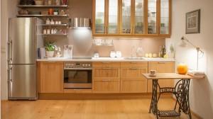 Dębowa kuchnia. Ta kuchnia jest fragmentem większej otwartej przestrzeni, w której mieszczą się jeszcze jadalnia, salon i hol. Świetnie dopasowana do potrzeb właścicielki, pomieściła wszystkie potrzebne sprzęty a pamiątkowe drobiazgi ozdobiły stalowe półki. Dodatkową powierzchnią blatu służy wiekowa maszyna do szycia Singer.