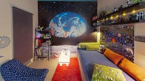 Pokój małego astronauty. Pokój z widokiem na Ziemię stał się wygodnym obserwatorium świata. Długie półki pomieściły niezmierzone kolekcje lego, a regał podręczną biblioteczkę. Całość dopełnia ciekawe i bezpieczne dla dziecka oświetlenie.