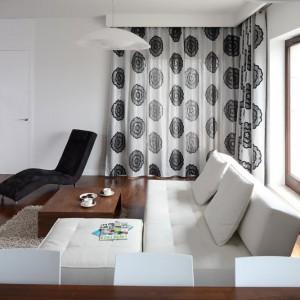 Biała tapicerowana kanapa oraz czarny szezlong tworzą miejsce na wypoczynek w pokoju. Dekorację są dobrane kolorystycznie zasłony. Fot. Bartosz Jarosz.