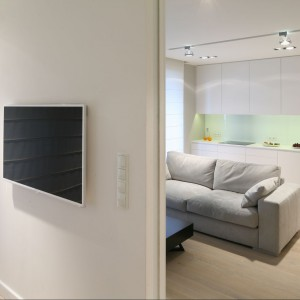 Wygodna kanapa plus zestaw kina domowego – niewielki salon to idealne miejsce do odpoczynku. Przesuwane drzwi do sypialni nie zajmują  miejsca. Fot. Bartosz Jarosz.
