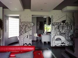 Loftowa aranżacja przestrzeni dziennej z monochromatycznym muralem na łączniku pomiędzy kuchnią a salonem.